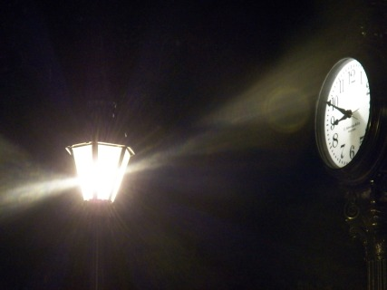 clock at night near a lamp