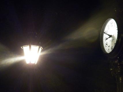 clock at night near a lamp